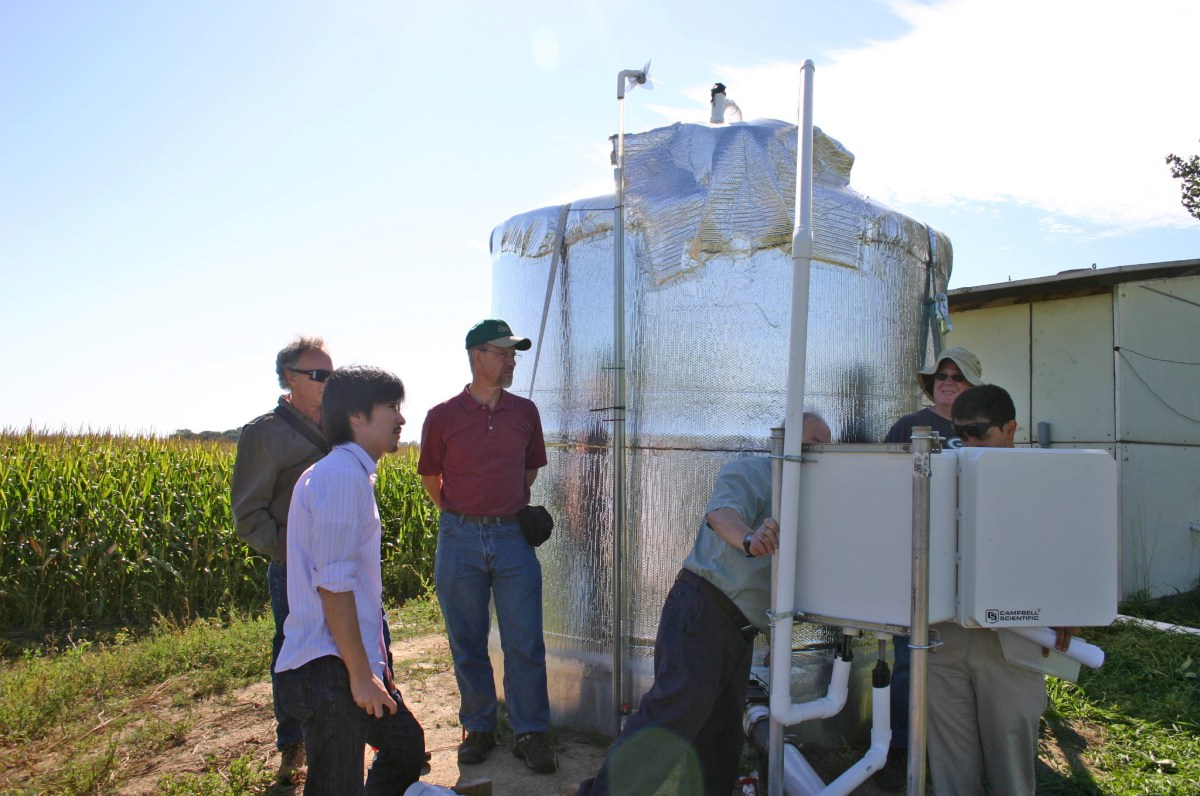 Researchers examine controls next to a large water storage tank, which supplies the bioreactor compartments with water at a stable pressure and flow rate. Credit: Michael Winikoff, BioTechnology Institute