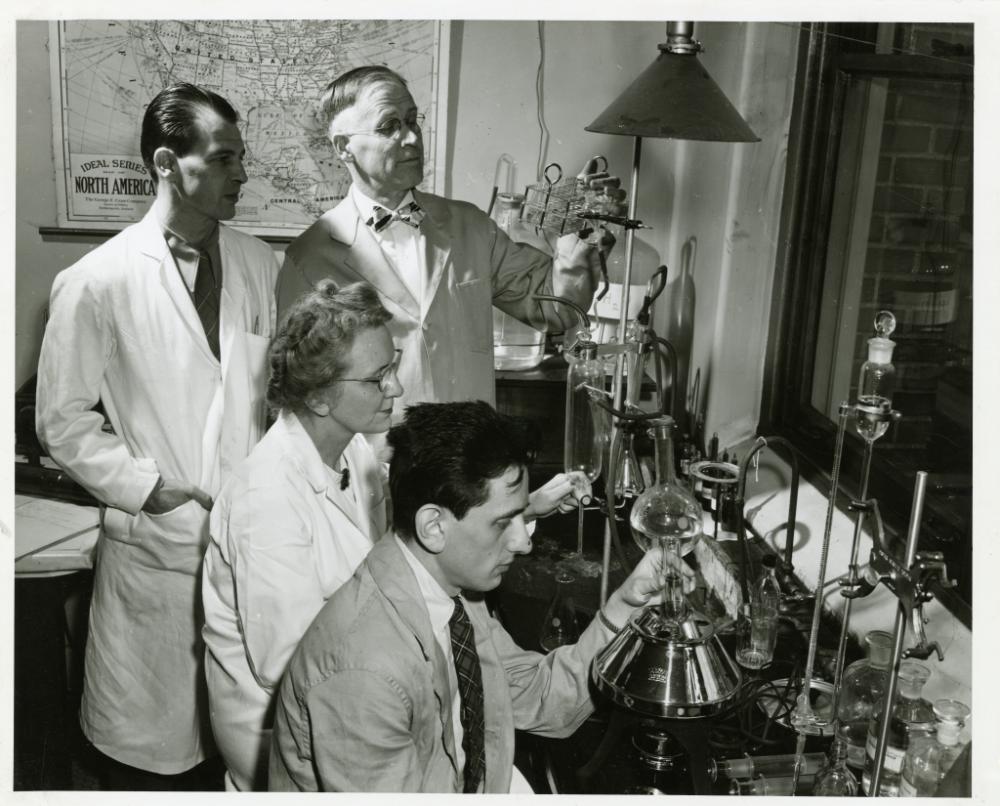 Halvor Halvorson, Cyril Stulberg and Helene Brumfield, gather around laboratory equipment