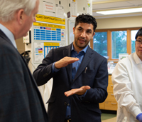 Dr. Abbas uses his hands to visually convey information while describing his research to an observer.