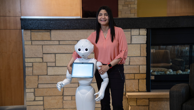 Arishia Khan stand besides her robot
