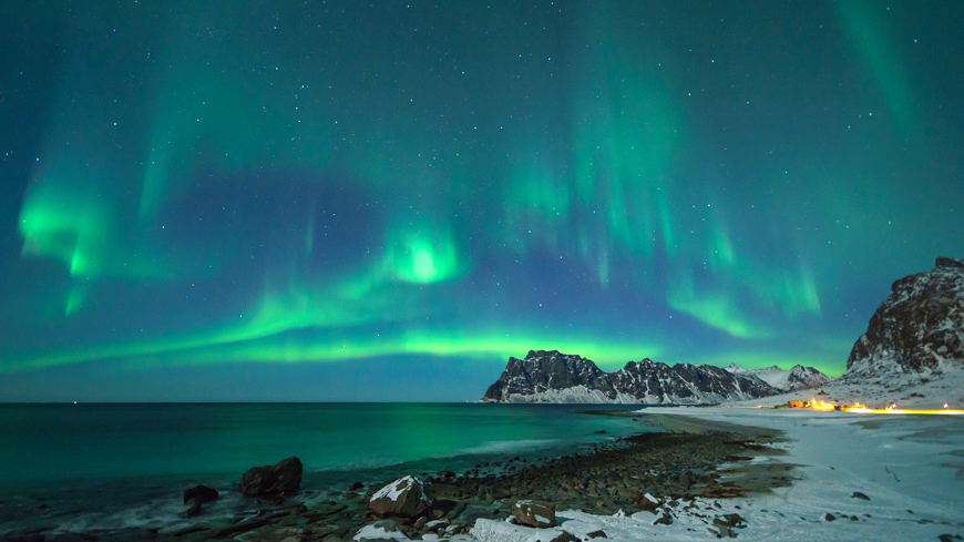 Aurora seen over water and mountains