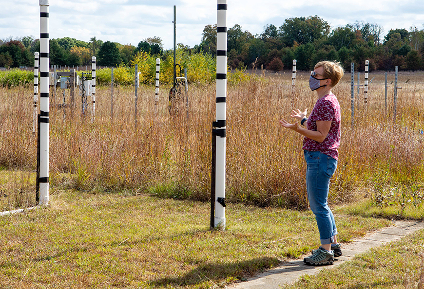 Woman standing outside next to large PVC pipes and plants