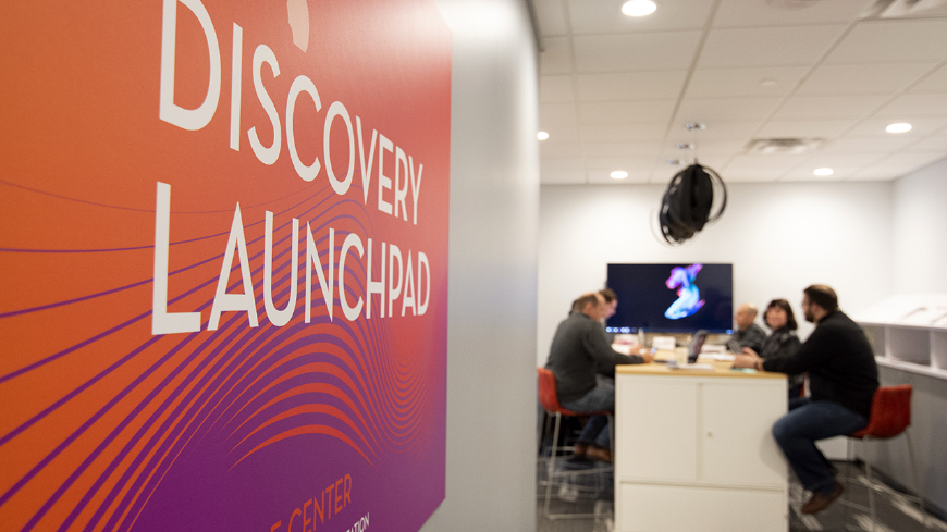 Entryway to the Discovery Launchpad with advisers meeting with entrepreneurs and researchers in the background
