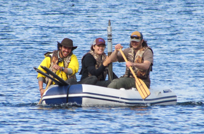 Researchers paddle an inflatable raft on a lake, with one holding a sediment core.