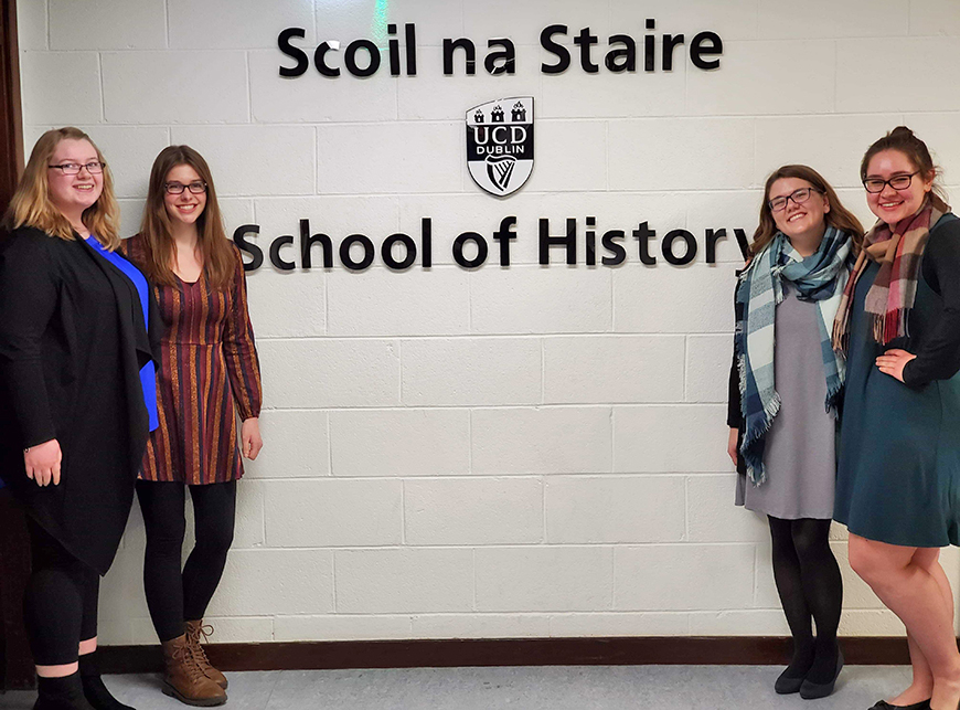 "Students pose for a picture next to a sign reading ""School of History"""