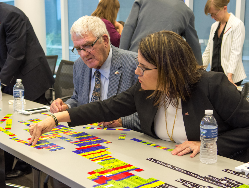 President Gabel and Regent Simonson work on a genomics tabletop game.