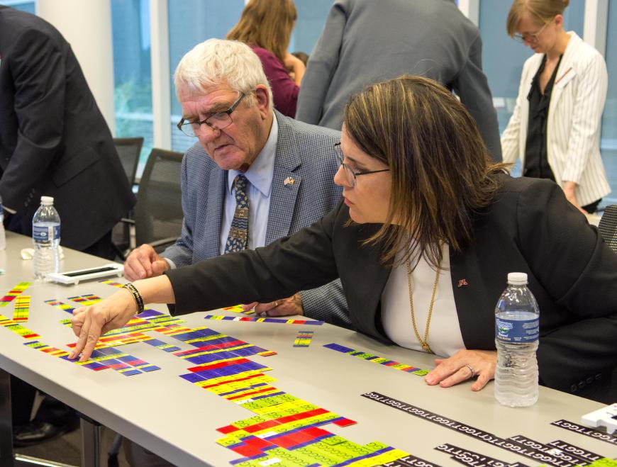 President Gabel and Regent Simonson work on a genomics tabletop game.