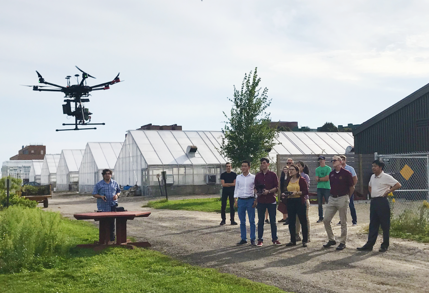U President Gabel and researchers watch a drone fly.