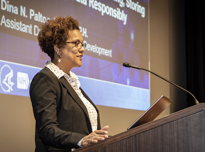 Dr. Dina Paltoo speaks at a podium