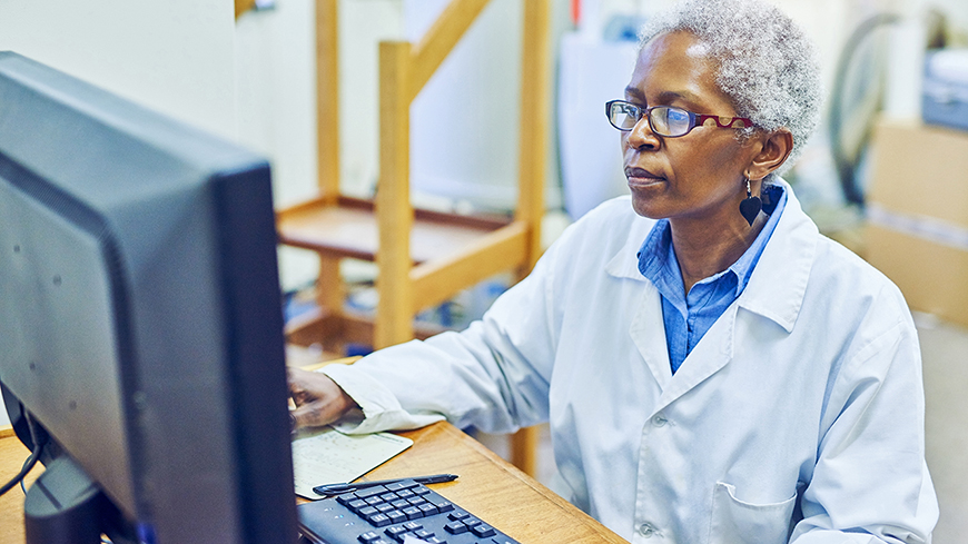 Woman in a lab coat using a computer