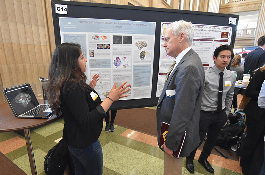 VP Cramer listens to a student researcher explain her work in front of a research poster at a poster session