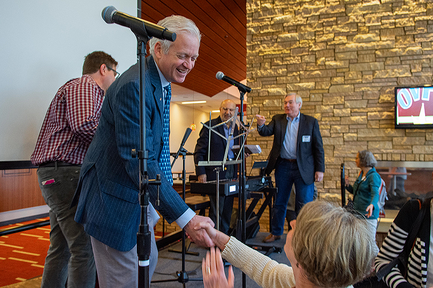 VP Cramer shakes hands with OVPR staff while standing on a stage next to musical equipment