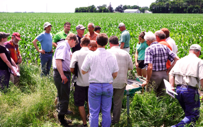 A group of people on a farm having a discussion