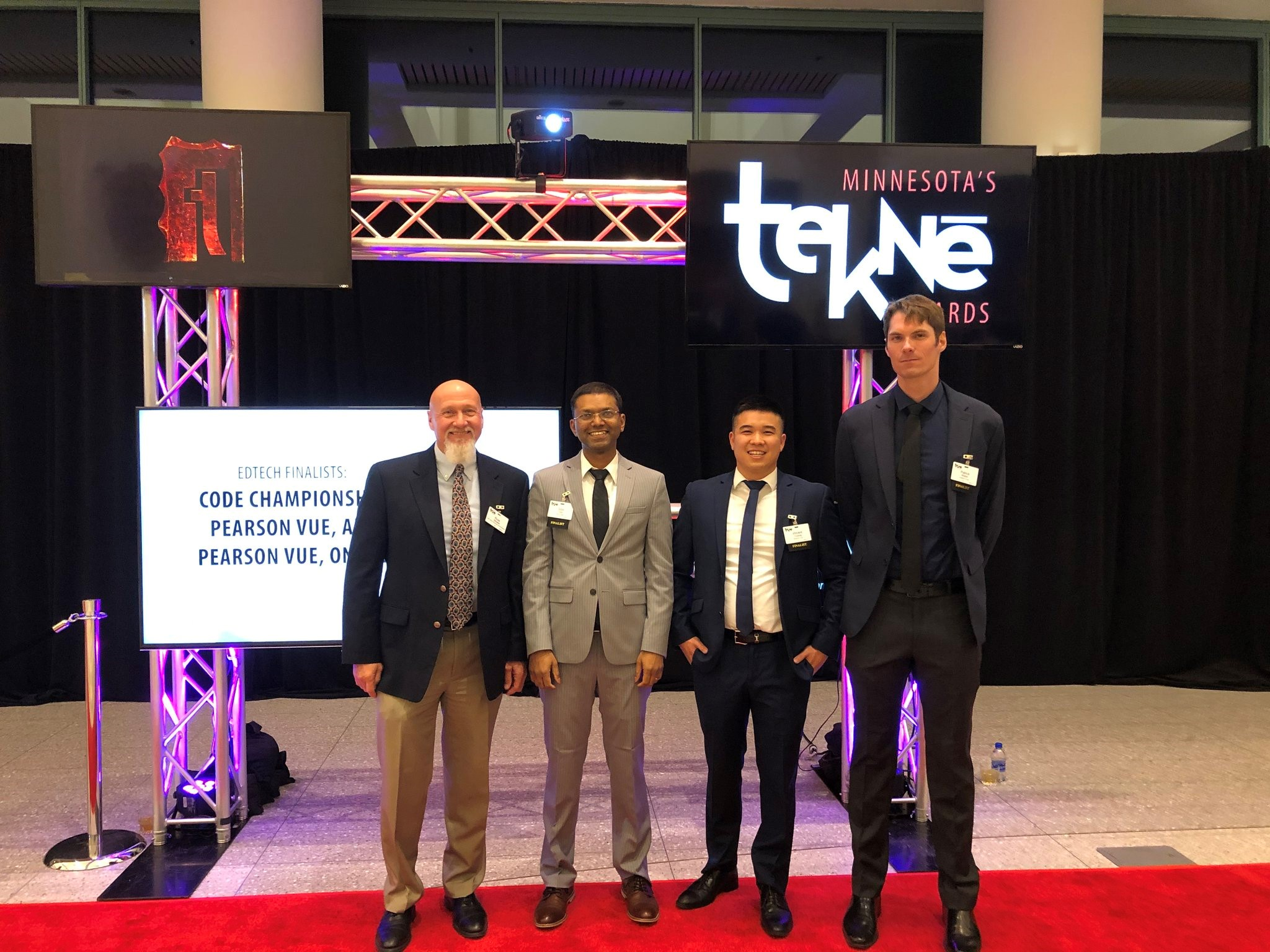 Four men in suits standing in front of a Tekne Awards red carpet picture spot