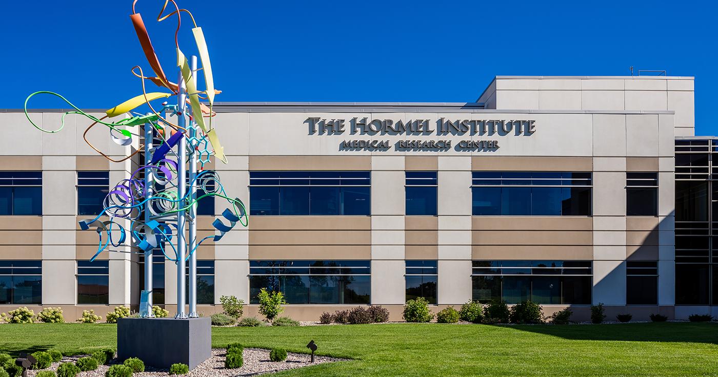 The Hormel Institute building exterior with sculpture in garden