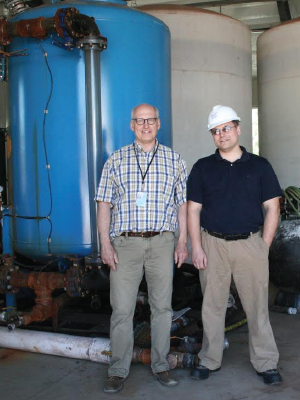 Peter Clevenstine (left) and Igor Kolomitsyn monitor a peat-based filtering system that cleans pollutants from the water used in mining.