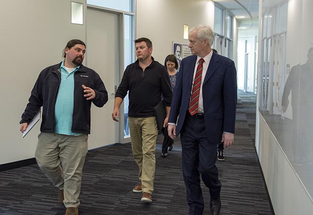 MCC group and VPR Cramer walk through hallway at MCC