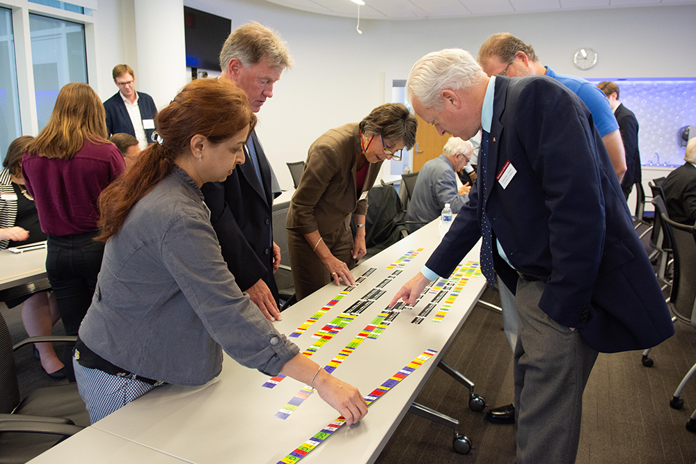 group standing at table interact with and puzzle over colorful slips of paper that representing a human genome