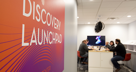 Entry to the Discovery Launchpad space, with advisers and participants sitting at a table together in the background