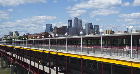 City skyline of Minneapolis rising in the background above a foreground view of Washington Avenue Bridge on UMN campus