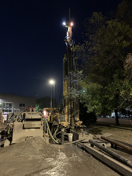 Drilling equipment shown at night at a job site where the ground is torn up