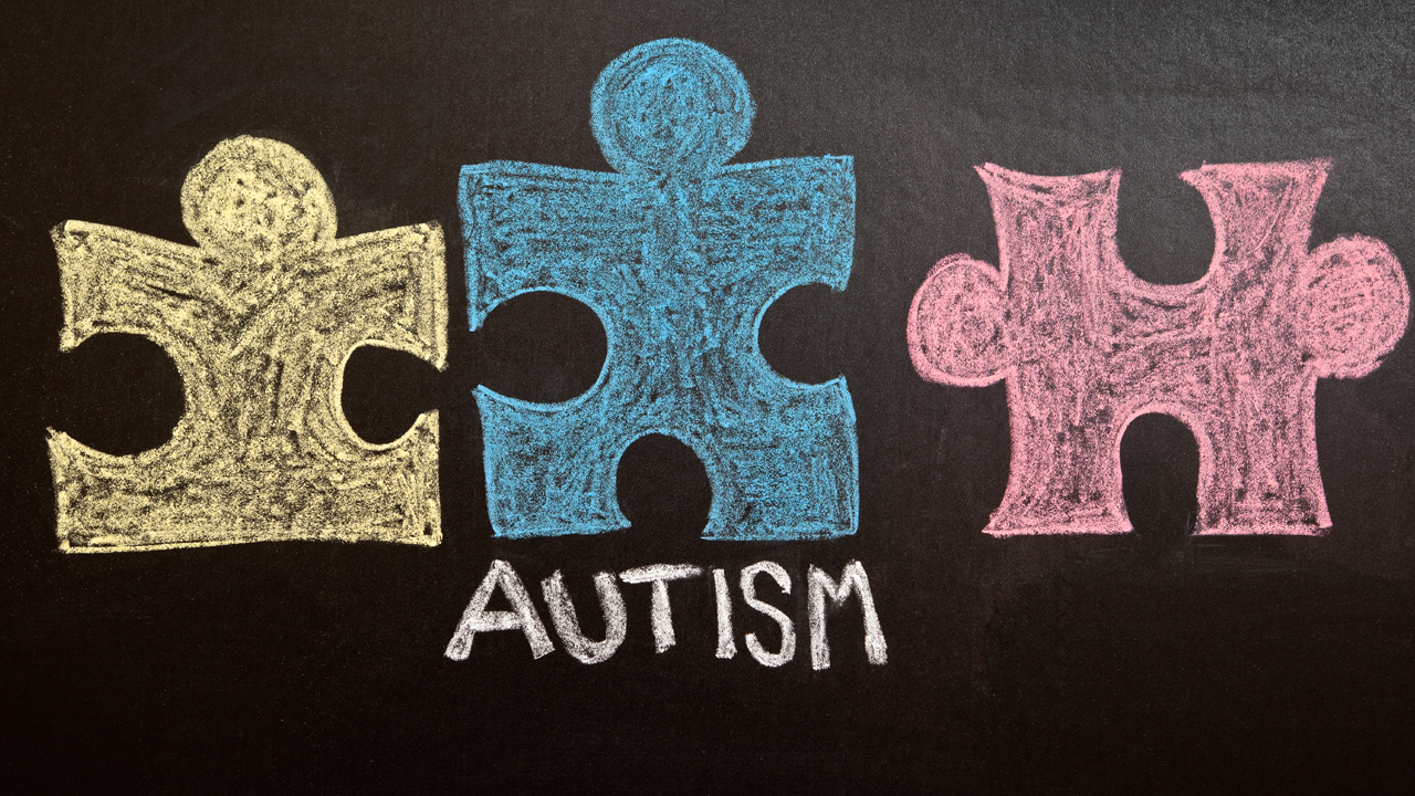 """Puzzle pieces on a chalk board, with the word """"Autism"""""""