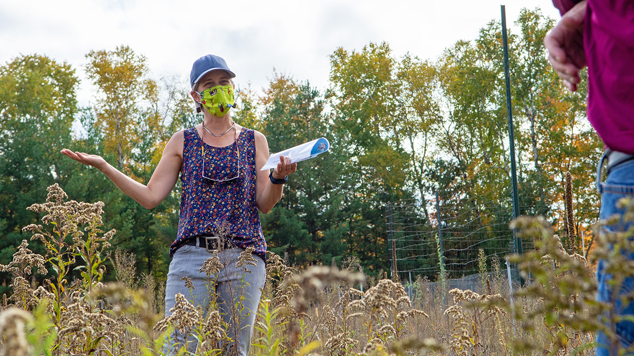Woman gesturing as she speaks while standing outside in grasslands