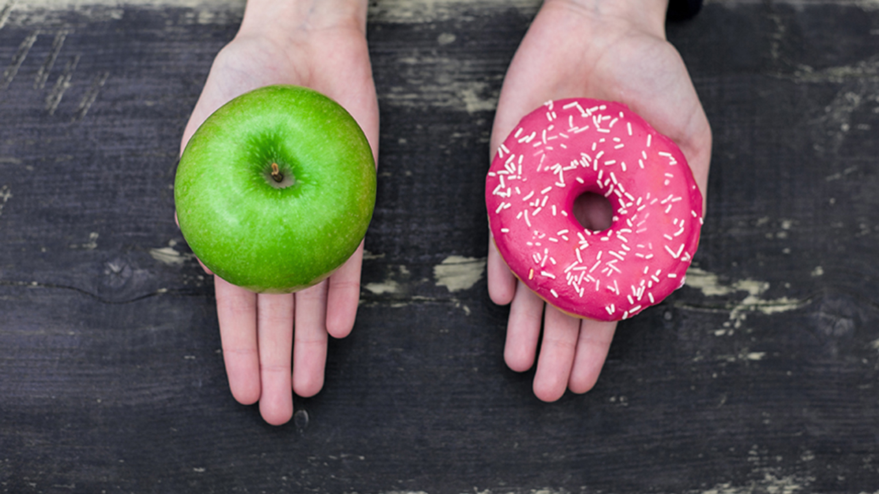 two hands, one holding an apple and the other holding a doughnut