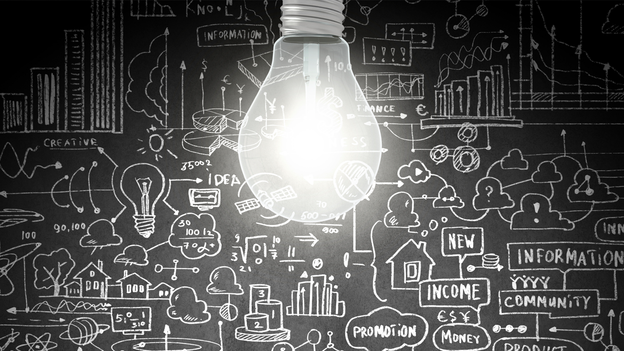 Lightbulb in front of a chalkboard with abstract drawings