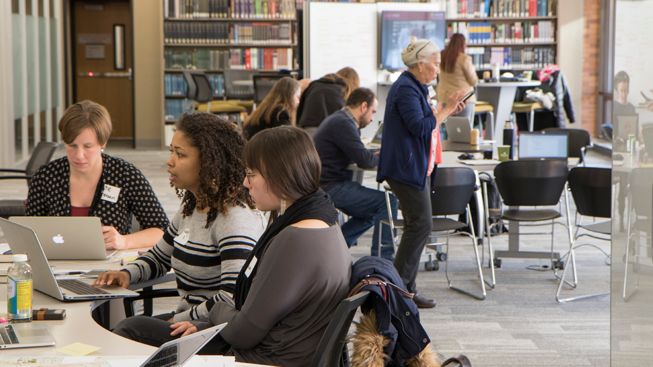 People studying and working in groups in a library