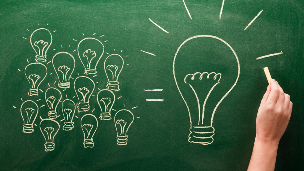 A hand drawing many small light bulbs next to one large light bulb on a chalkboard