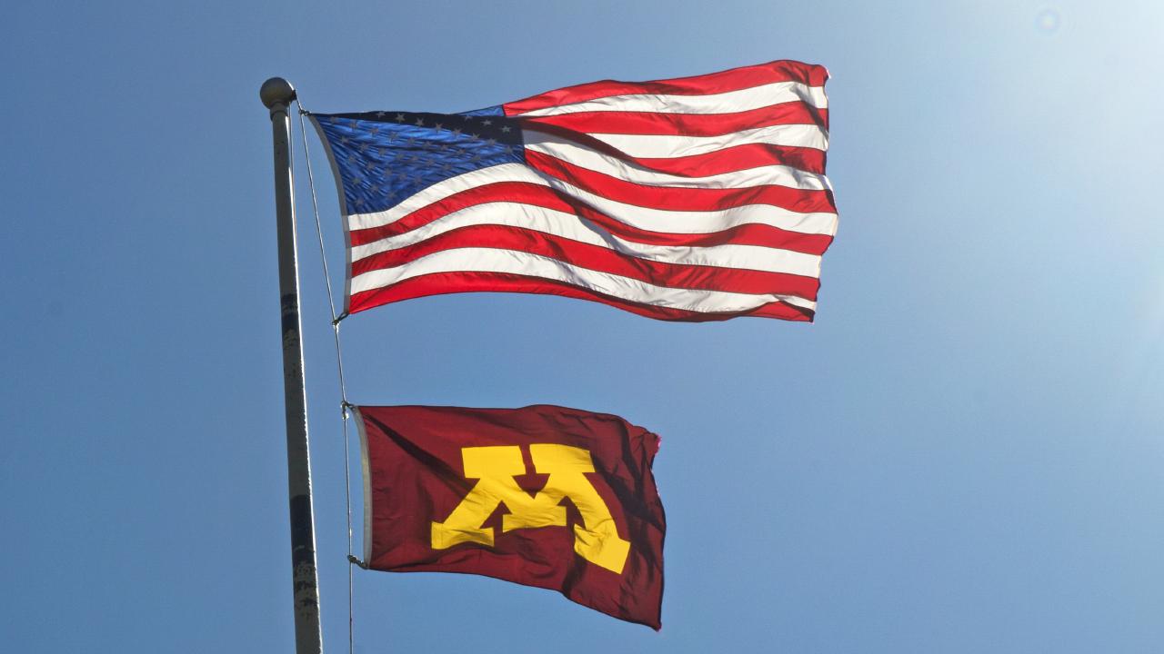 Flag pole with US flag and U of M flag
