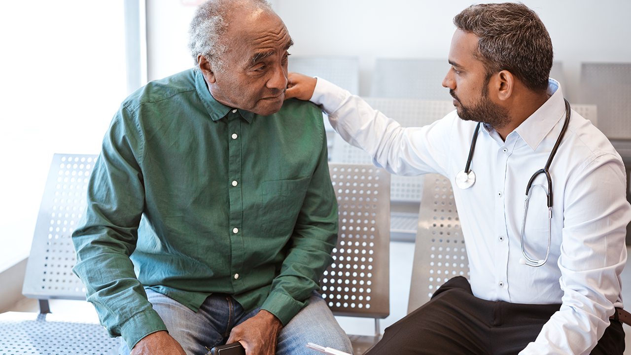 Health care professional speaking to elderly man