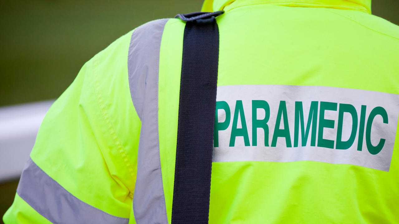 "A person wearing a yellow jacket with the word ""paramedic"" across the back"