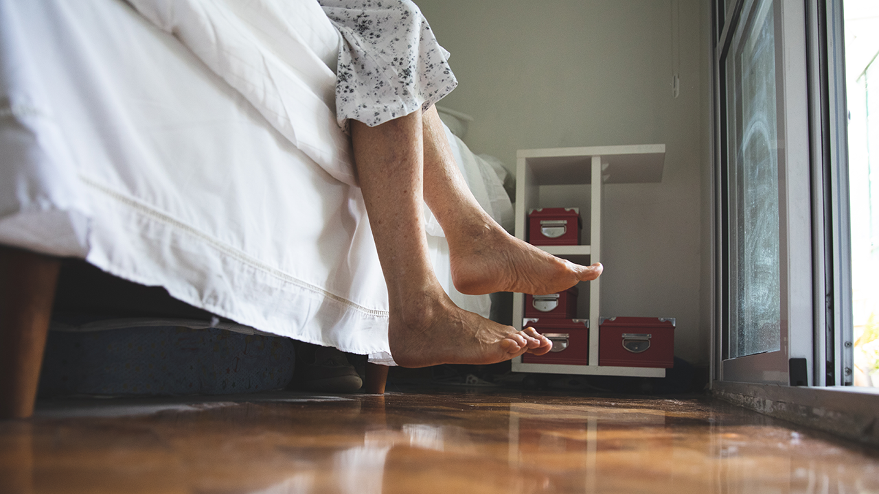 A patient's feet hang over the side of a bed