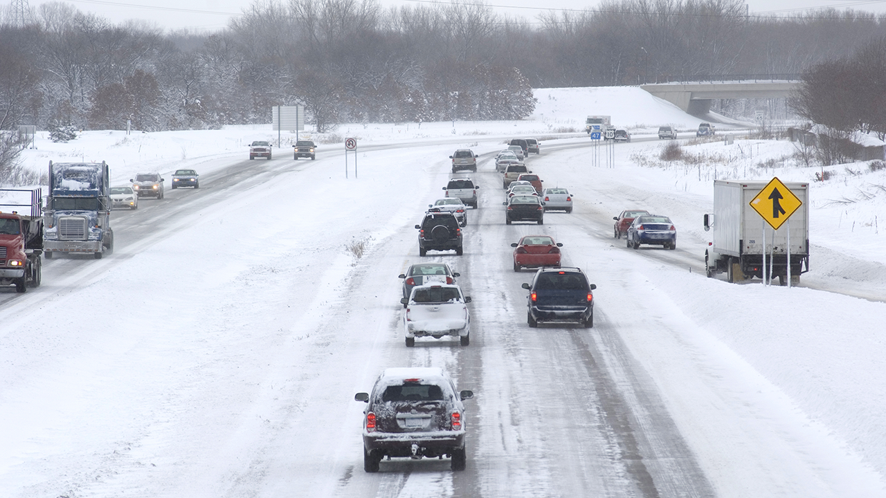 Cars and trucks driving on a divided Minnesota highway in snow