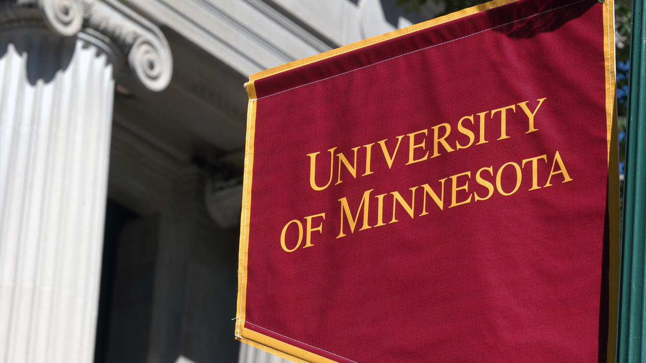 A U of M flag near a building with columns