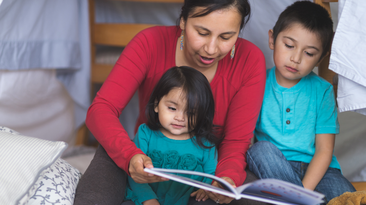 Native American mother reading to her son and daughter in a blanket fort