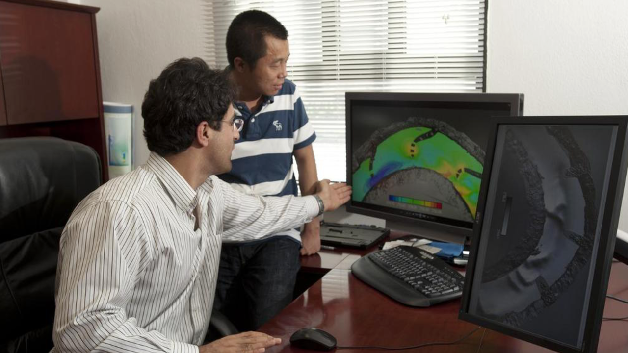 Researchers using software at a desk, looking at a computer screen together
