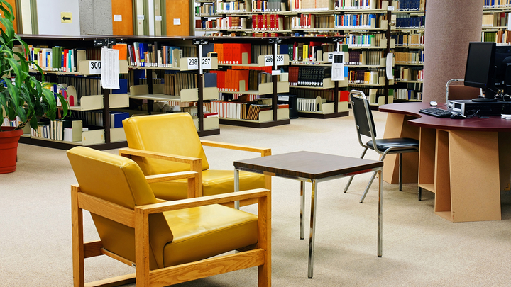 Interior of a library, with chairs, tables, a computer, and shelves of books