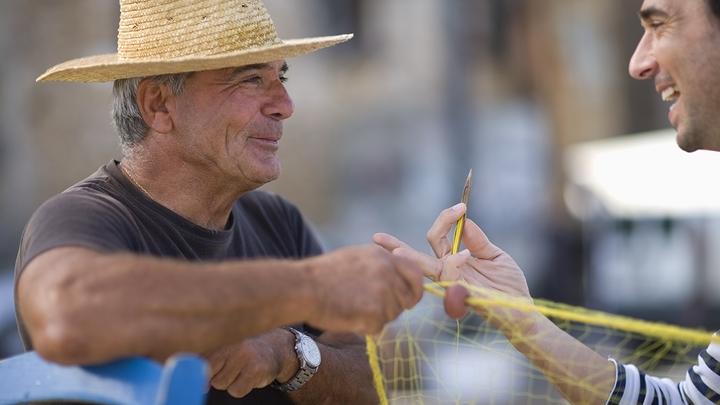 Elderly European man speaks with younger man