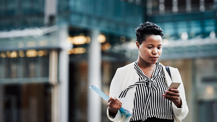 Woman in business apparel checking a phone in a downtown setting