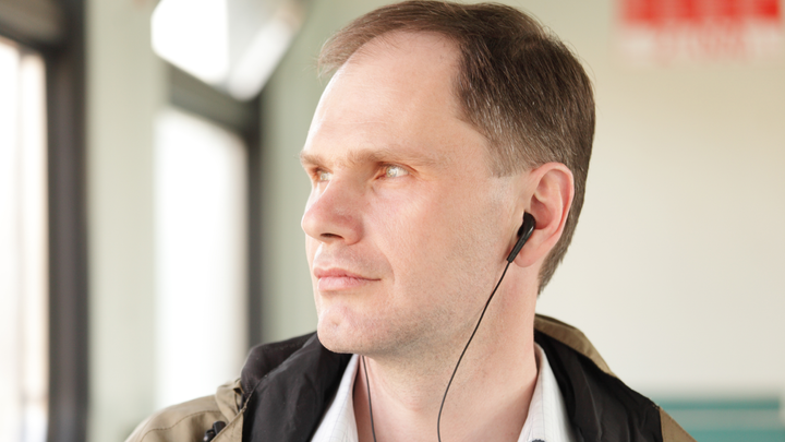 Man listening to a podcast through earphones