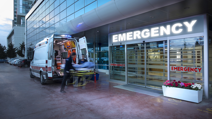 Emergency medical workers arrive at a hospital in an ambulance