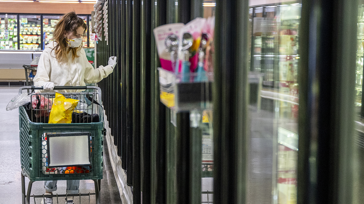 Woman looking at frozen foods while pushing a shopping cart in a grocery store