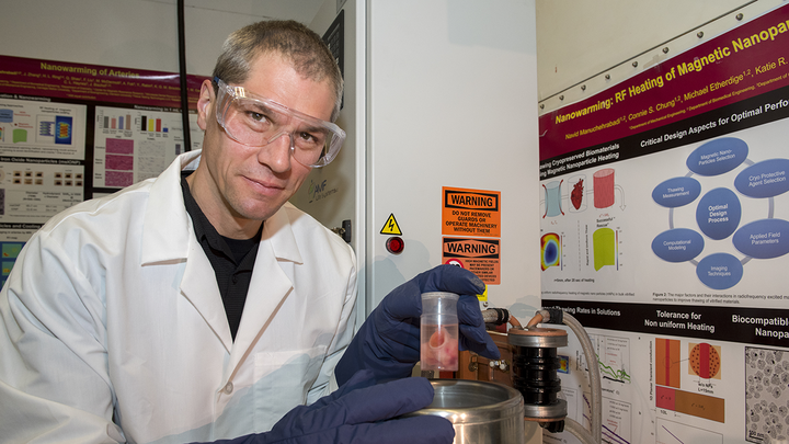 Man in lab coat holding scientific equipment