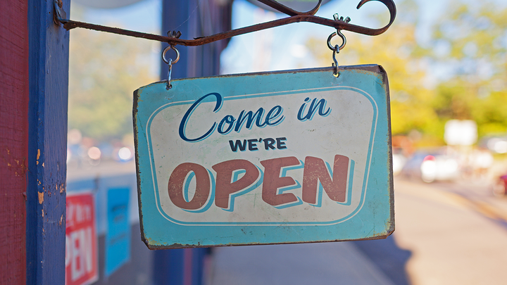 "A sign reading ""Come in, we're open"" hangs outside of a store"