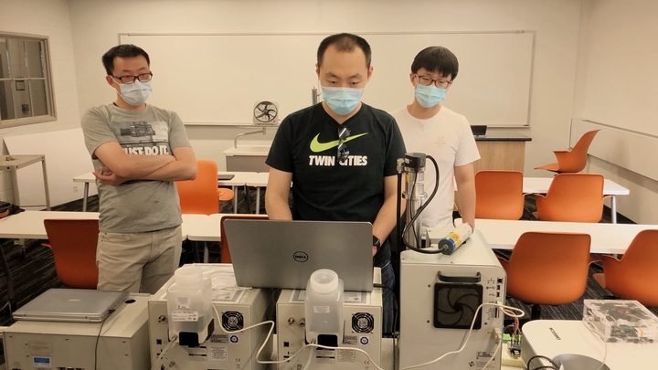 Researchers operate laboratory equipment that has been set up in a classroom setting.