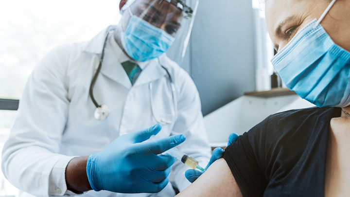 Doctor wearing mask and face shield administers a vaccine to a patient