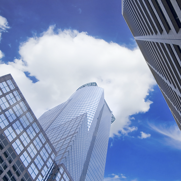 View of towering commercial buildings reaching up toward a blue sky